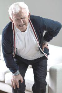 a man winces as he grabs his hip